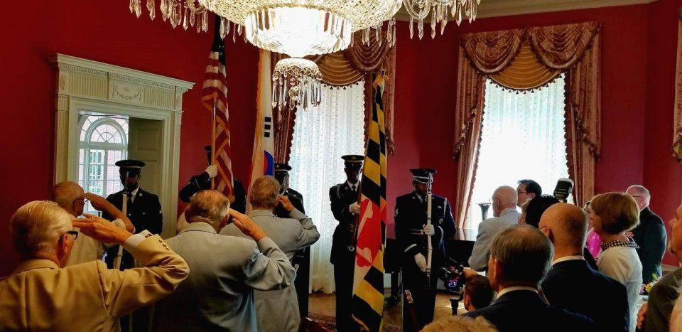 참석자들이 국기에 대한 경례를 하고 있다.